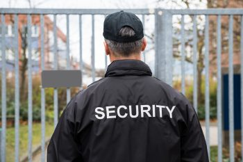 Security guard standing in front of a fence
